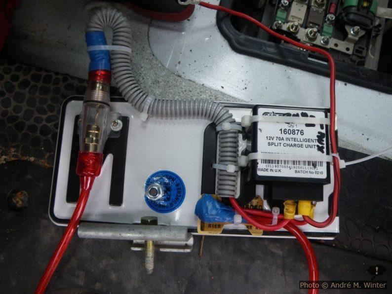 70A-Trennrelais zur Steuerung der Zweitbatterie: Links eine 40A-Sicherung (das Kabel kommt von der Startbatterie), rechts unten das Kabel zur Zweitbatterie, oben der Masseanschluss für das Relais. Unten der Winkel und die Fixierschraube der Startbatterie im Batteriekasten unter dem Fahrzeugboden. Da der Batteriekasten gut Spritzwassergeschützt ist, reicht diese offene Bauweise.