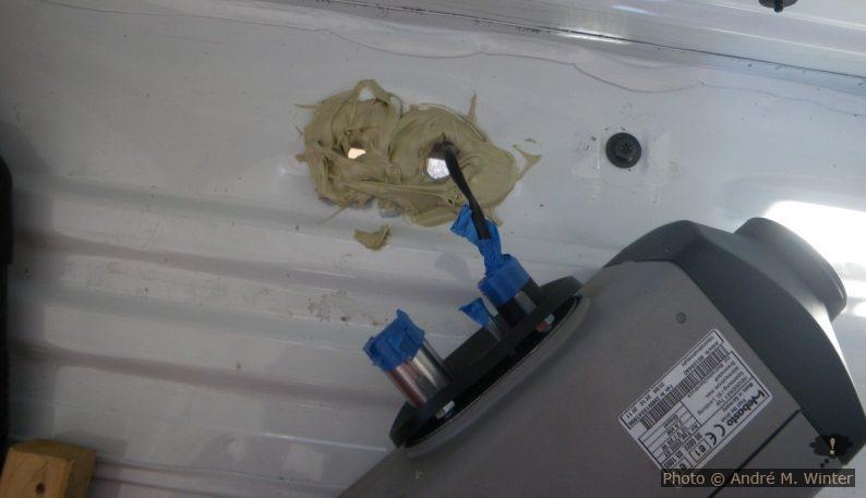 Die Stelle entspricht nicht ganz den Voraussetzungen, denn sie ist nicht eben. Ich habe alles mit einen dicken Patzen Teroson abgedichtet. Am Ende zieht man mit den vier Schrauben diese gewölbte Bodenplatte ohne hin flach... Im Bild an der Anschlussstelle: Auspuff (Metall). dünne Dieselzufuhr (Metall). Frischluftzufuhr für den Brenner (Kunststoff), hier noch mit der Stromversorgung der Dieselpumpe, diese geht später durch das Gewinde der Gepäcksschraube rechts, die ohnehin durch die Heizung verdeckt wird.