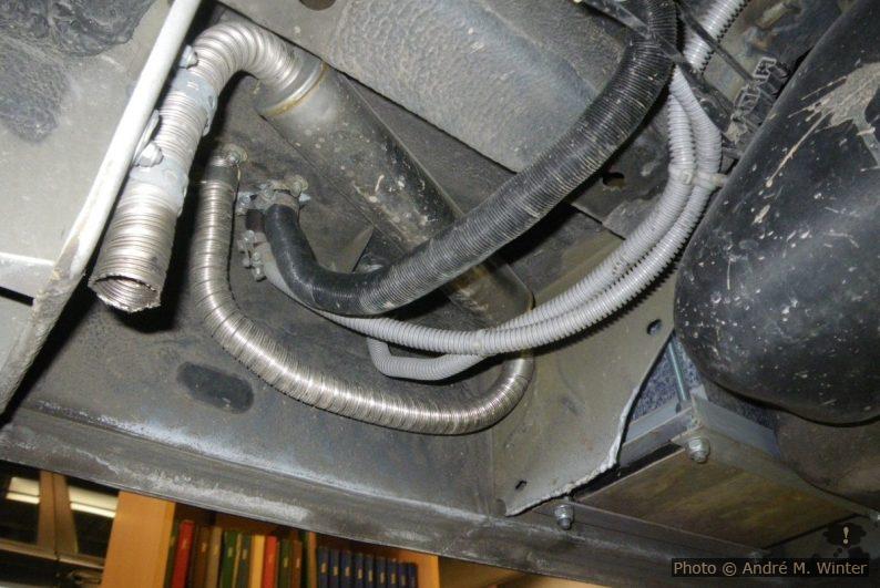 Der Auspuff macht hier eine vertikale Schlinge und es kann somit zu Kondenswasserstau kommen. Nach nun fünf Winterperioden, inklusive zwei Wochen Norwegen im März, konnten keine Probleme festgestellt werden. silber: Auspuff (Richtung egal). schwarz: Frischluftzufuhr für den Brenner. grauer Kabelschlauch dazwischen: die Dieselzufuhr. grauer Kabelschlauch rechts: Strom für die Dieselpumpe. Die Kabelschläuche laufen zusammen hinter den Tank, getrennt über den Tank (durch je zwei ausreichend grosse Löcher in den Querträgern, die Kabelstrang der Handbremse läuft durch die mittleren Löcher), anschliessend wieder zusammen vor dem Tank auf die rechte Seite am rechten Träger entlang bis zur Pumpe und zur Anschlussstelle.