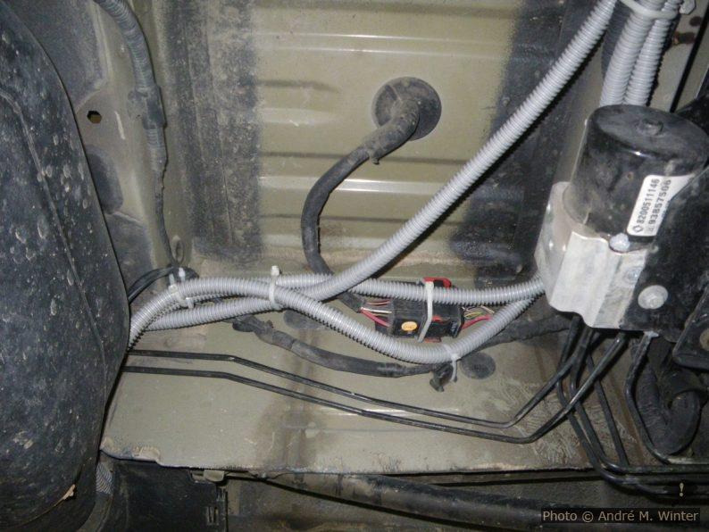 Die grauen Kabelrohre sind Nachrüstungen für die Zweitbatterie (in einem Schacht an der linken Aussenseite in Wagenmitte) und Verbindungen zur Kraftstoffpumpe der Standheizung (am rechten Längsträger). Rechts ein Teil der ABS-Anlage und wegen dieser Anordnung kann man nicht einfach den Batteriekasten gegen einen grösseren für zwei Batterien austauschen.