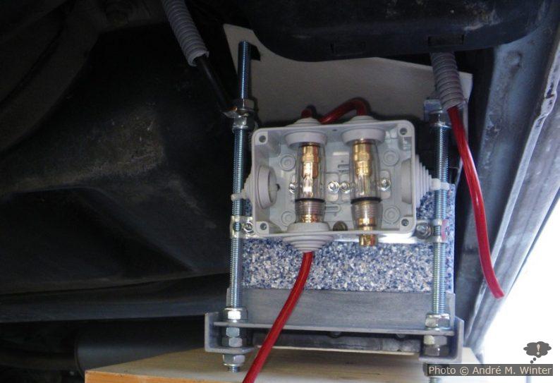 Eine Sicherung für die Strecke zur Startbatterie und die zweite für den Weg zum Schaltkasten im Inneren des Wagens. Die Kabelbox ist definitiv zu klein für die grossen Sicherungen, aber ich hatte keine andere. Auch sind die ausgehenden Pluskabel nicht ausreichend gegen Steinschlag geschützt (sie sollten alle oben rausgehen). Die Masse führt zurück zur Startbatterie.